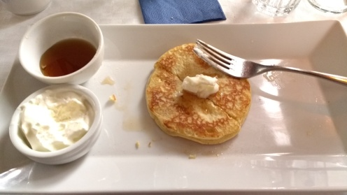 American pancakes with whipped cream and maple syrup